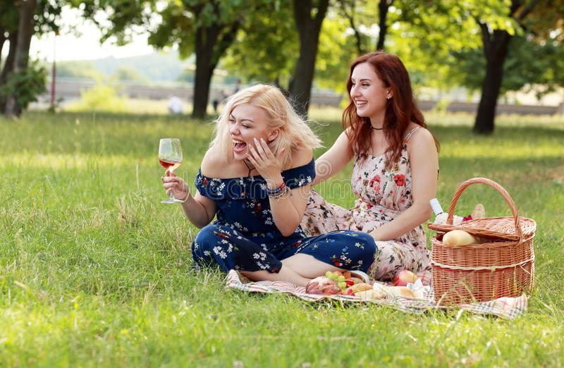 Girl friends have fun. Drink wine celebrate friendship on picnic laughing and joking royalty free stock images
