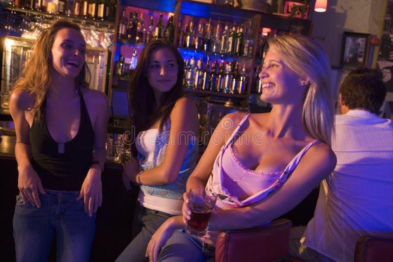 drinkar har tre unga kvinnor arkivfoto
