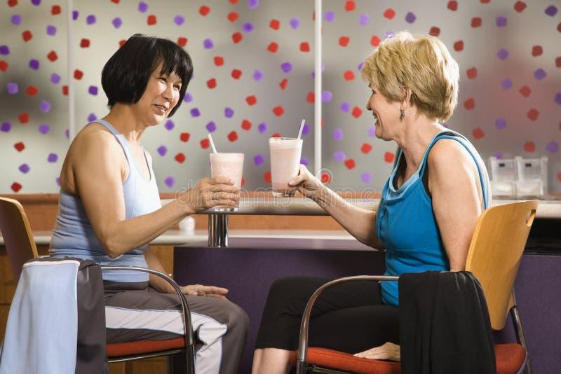 drinkar som sitter kvinnor royaltyfri fotografi