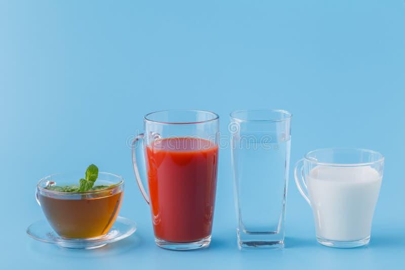 Drinken de groeps Nuttige Kleurrijke Dranken Melkthee Juice Water op Blauwe Achtergrond stock fotografie