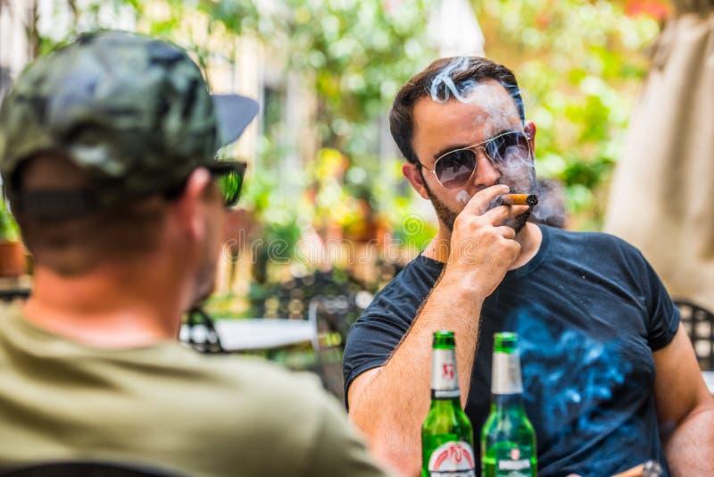 Drinkende bieren en het roken van een sigaar stock foto's