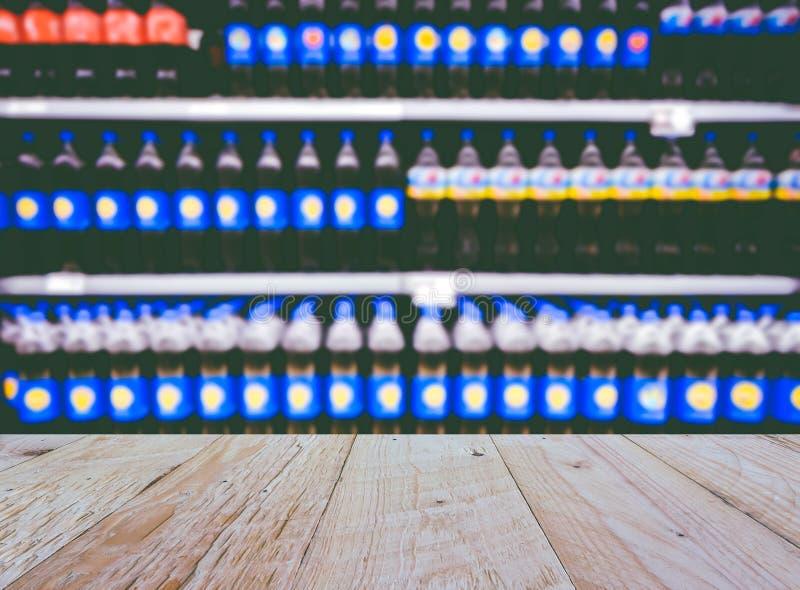 Drinkflaskor på skärm på hyllor i en supermarketsuddighetsbackgr arkivbild