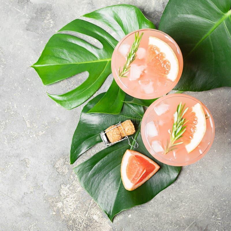 Drinkgrapefruktrosmarin och eleganta exponeringsglasbägare för is itu på grå konkret bakgrund Fyrkantig ramsikt från över royaltyfri bild
