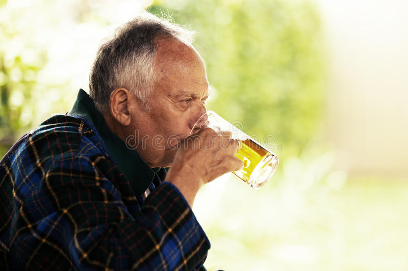 Drinking beer. Senior man is drinking beer. Sunny day royalty free stock photos
