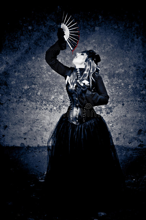 Drinking blood. Witch in black dress drinking blood dripping from a fan royalty free stock images