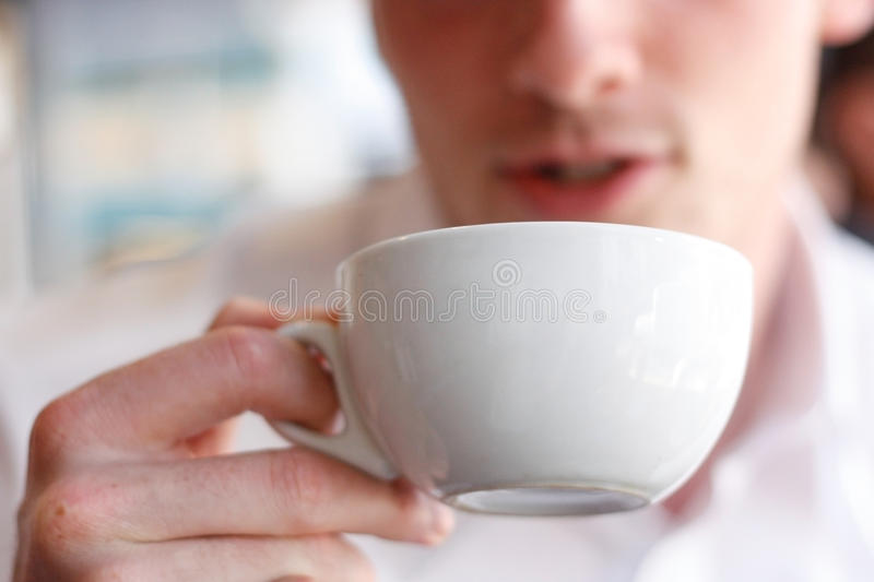 Drinking coffee. A man drinking coffee in a cafe stock images