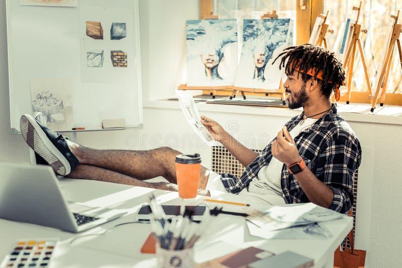 Bearded dark-haired interior designer drinking coffee and working. Drinking coffee. Bearded dark-haired interior designer drinking some coffee and working hard stock photos