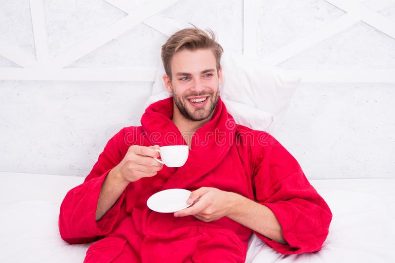 Drinking coffee for breakfast. Happy guy drinking coffee in bed. Bearded man in bathrobe holding drinking cup and royalty free stock photos