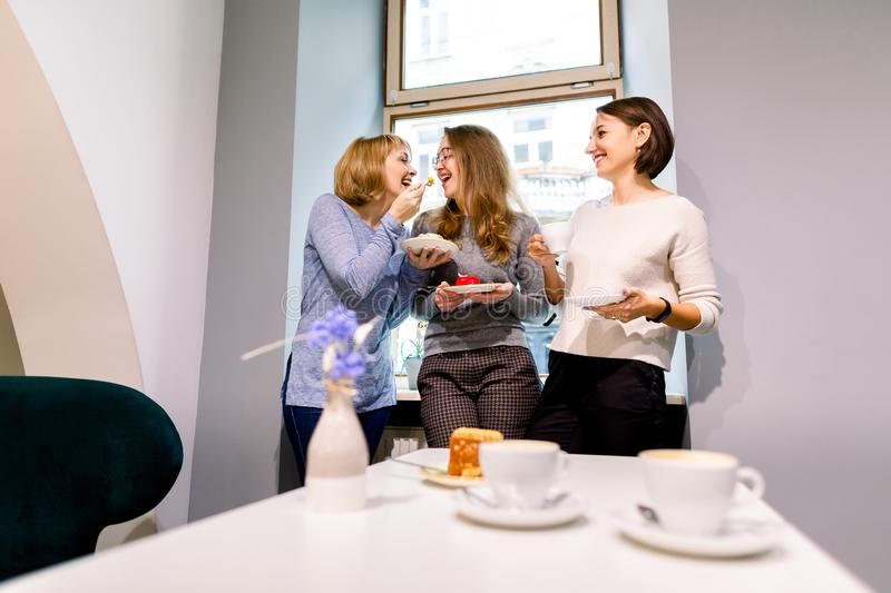 Drinking coffee and eating desserts together. Three beautiful women holding plates with delicious cakes desserts in cafe. Standing near the window. Meeting of stock photo