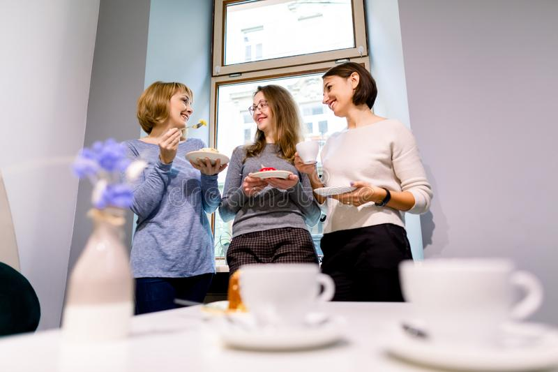 Drinking coffee and eating desserts together. Three beautiful women holding plates with delicious cakes desserts in cafe. Standing near the window. Meeting of royalty free stock image