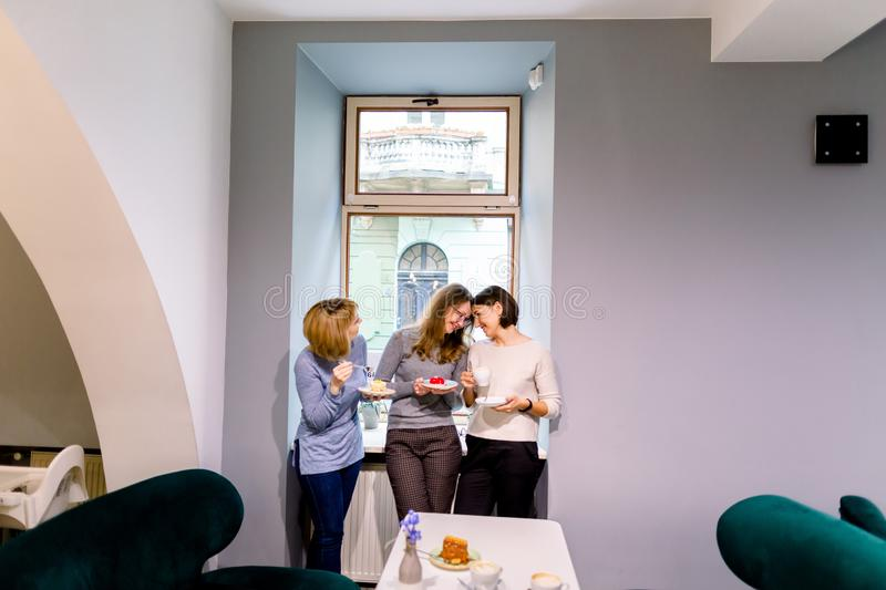 Drinking coffee and eating desserts together. Three beautiful women holding plates with delicious cakes desserts in cafe. Standing near the window. Meeting of stock photography