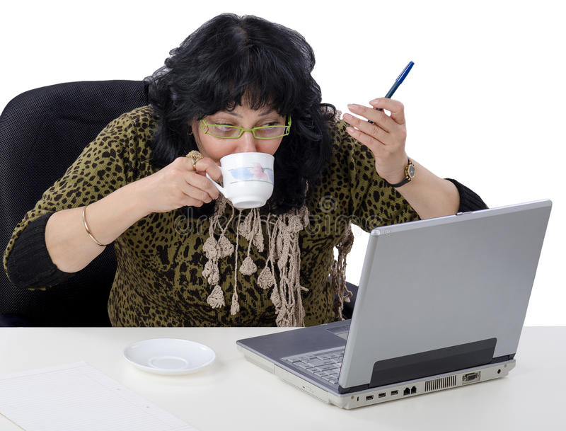 Drinking coffee during elearning lesson. Woman drinks coffee during online lesson in the internet royalty free stock images
