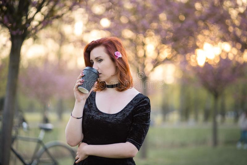 Drinking coffee from paper mug cup - Happy young travel dancer woman enjoying free time in a sakura cherry blossom park stock photography