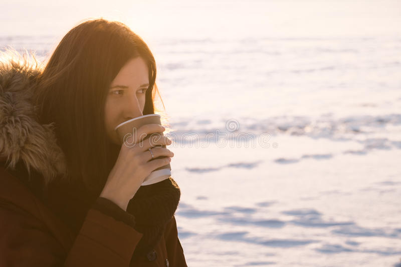 Drinking coffee to go in winter royalty free stock images