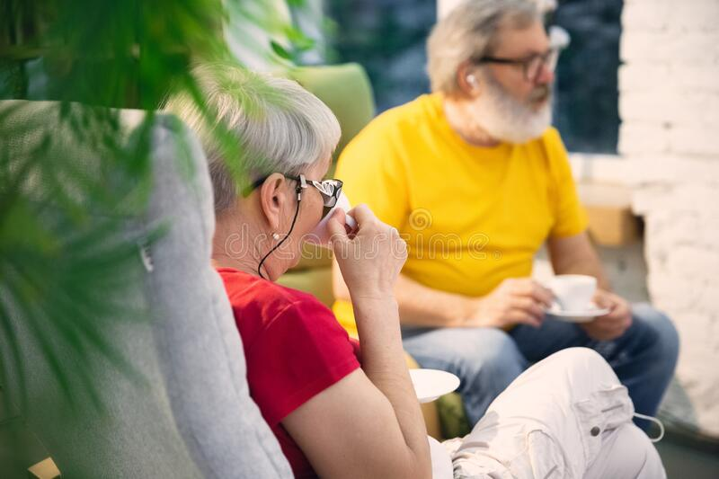 Couple of seniors spending time together being quarantined - caucasians mature and retired man and woman using modern stock photo