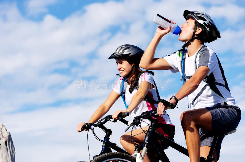 Drinking cyclist. Cyclist drinking water to ensure hydration and to quench thirst stock image