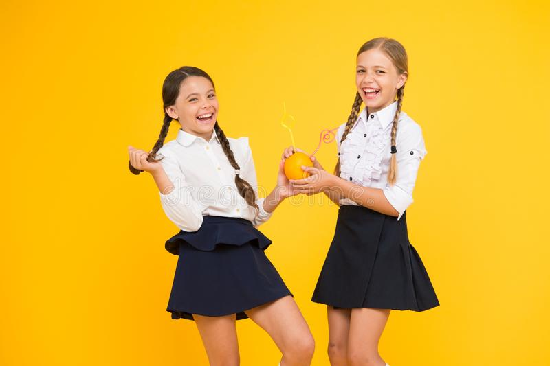 A drinking food. Little girls enjoying liquid vitamin food on yellow background. Small schoolchildren drinking citrus. Juice from orange fruits. Healthy organic royalty free stock images