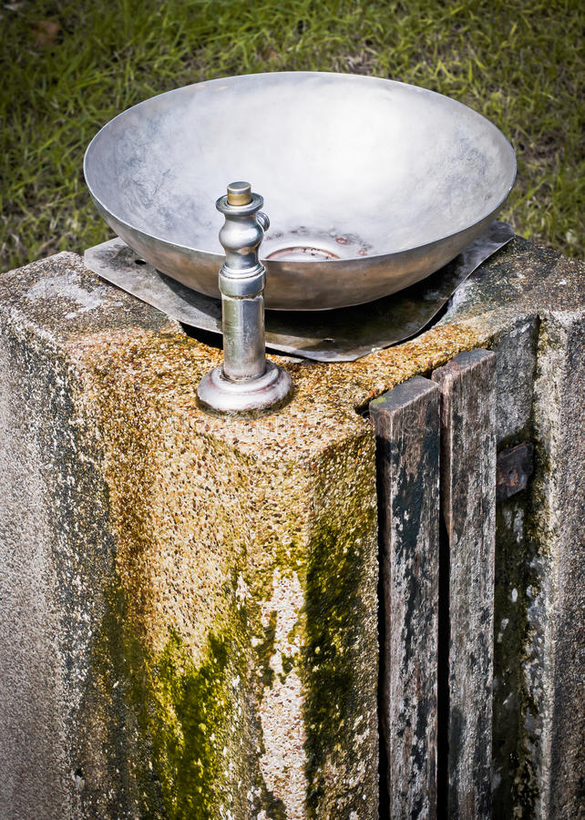Drinking fountain on Old stone pillar royalty free stock images