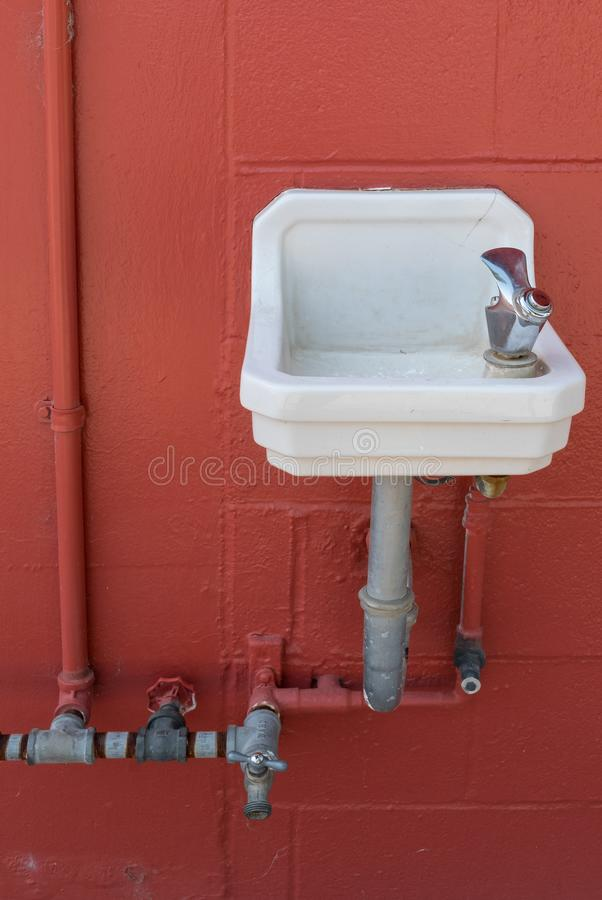 Drinking fountain and red wall royalty free stock photos