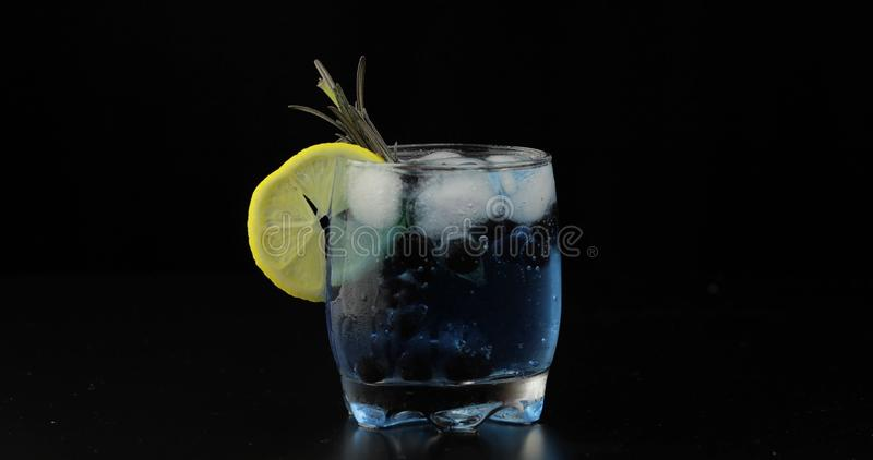 Drinking glass with cold drink. Refreshing soda lemonade blue cocktail royalty free stock image