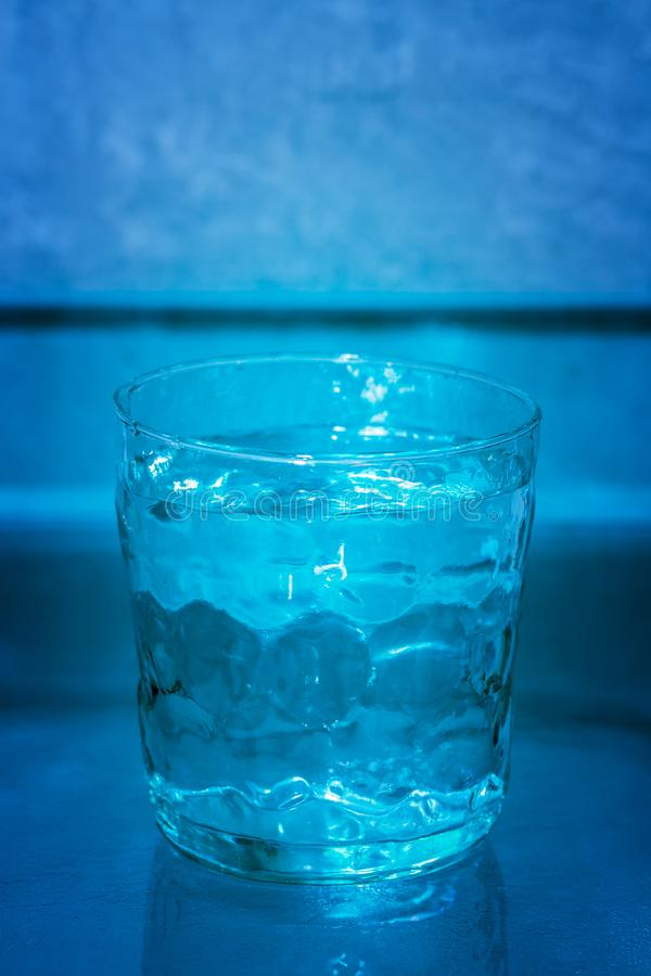 Drinking glass filled with water, full. stock image
