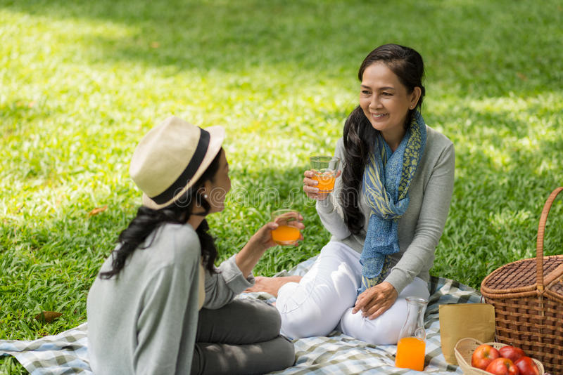 Drinking juice and gossiping stock image
