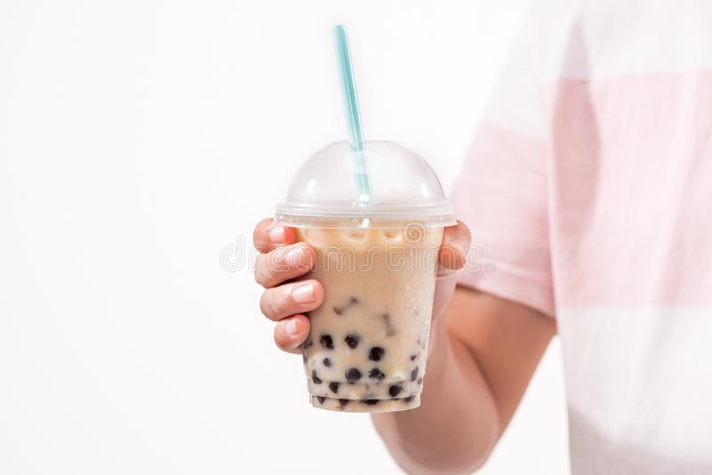 Drinking light brown creamy bubble tea and black tapioca pearls. In plastic cups on table royalty free stock photos