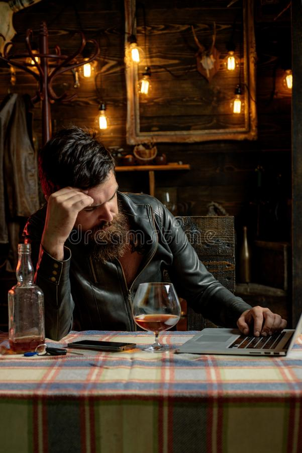 Drinking man. Man with beard holds glass brandy. Man holding a glass of whisky. Sipping whiskey. Degustation, tasting. Macho is drinking whiskey by his laptop royalty free stock photography