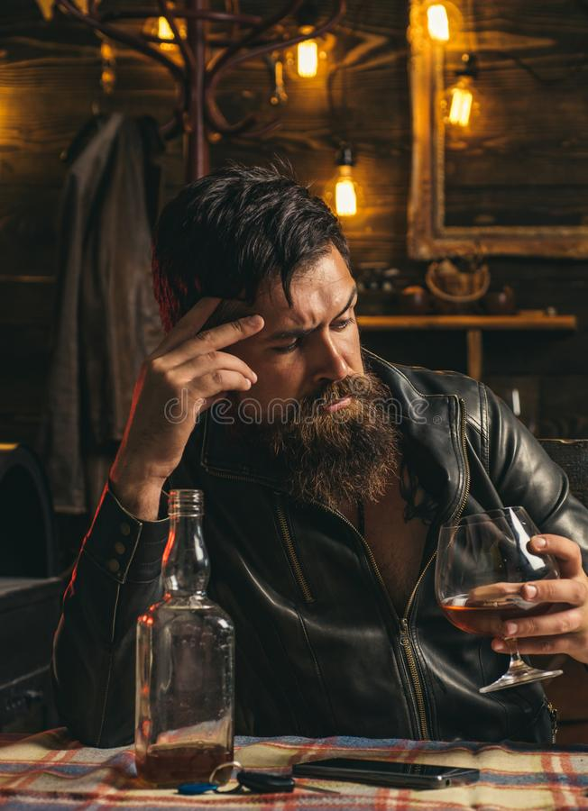 Drinking man. Man with beard holds glass brandy. Man holding a glass of whisky. Sipping whiskey. Degustation, tasting. Macho is drinking whiskey by his laptop royalty free stock images