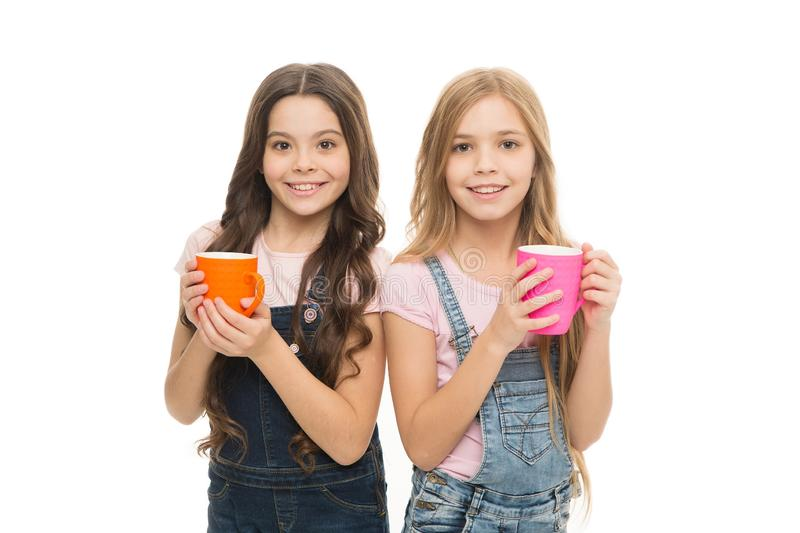 Drinking milk for good health. Cute kids taking a drink of tea with milk. Small children holding cups with warm milk royalty free stock images