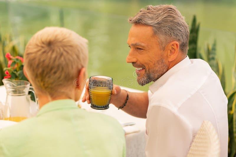Husband drinking orange juice having breakfast with wife royalty free stock images