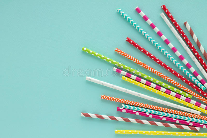 Drinking paper colorful straws for summer cocktails on light blue background. royalty free stock images