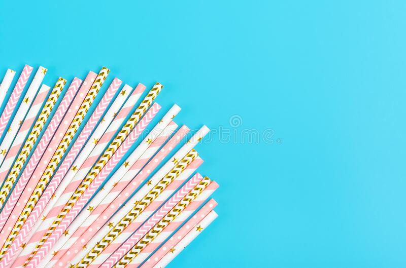 Drinking paper straws for party with golden, white, pastel pink stripes on blue  background. With copy space. Top view of colorful paper disposable eco royalty free stock images