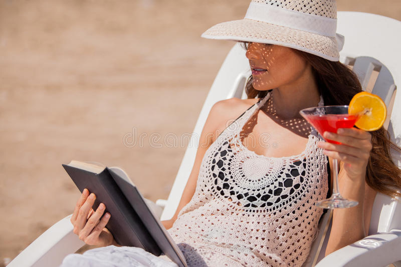 Drinking and reading at the beach. Relaxed young woman reading a book and drinking cocktails on her beach vacation stock photography