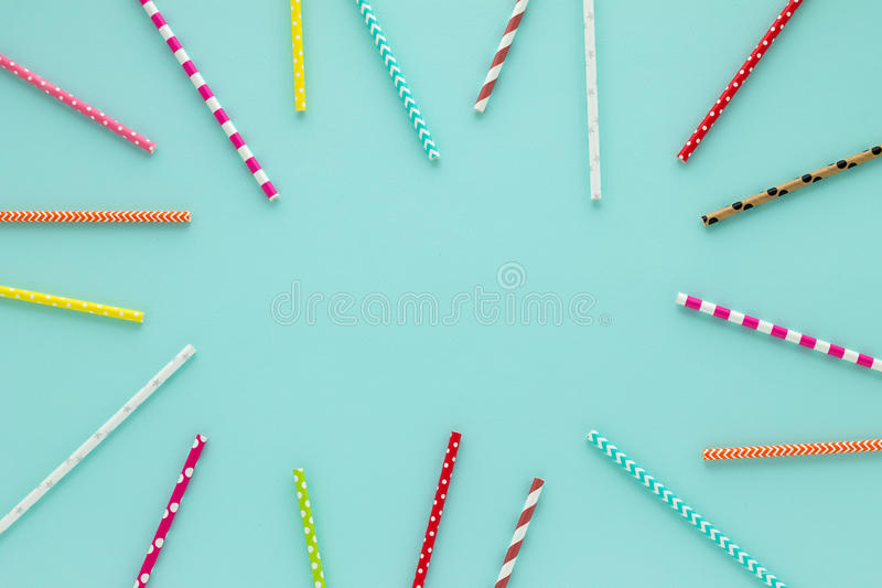 Drinking straws for party on blue pastel background with copy space. Top view of colorful paper disposable eco-friendly straws for summer cocktails stock photos