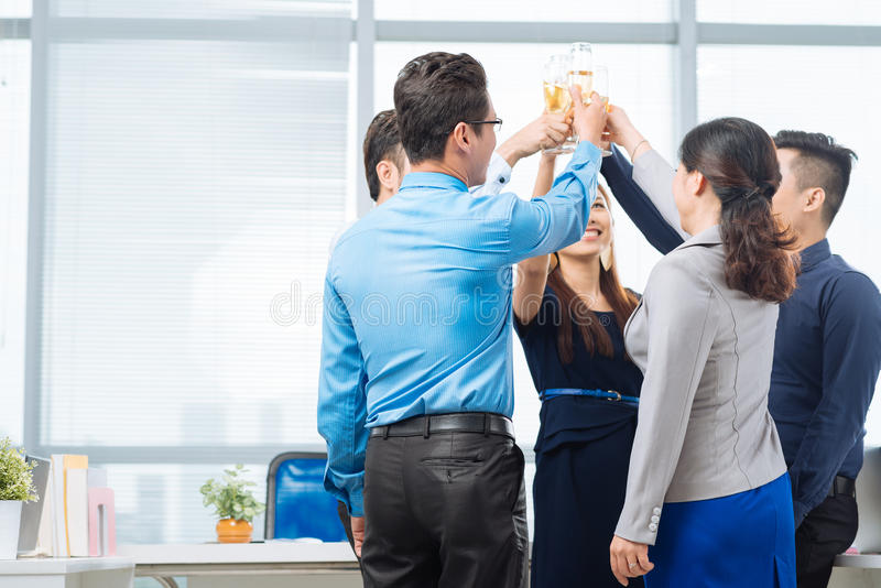 Drinking for success. Asian business people raising hands with champagne glasses stock image
