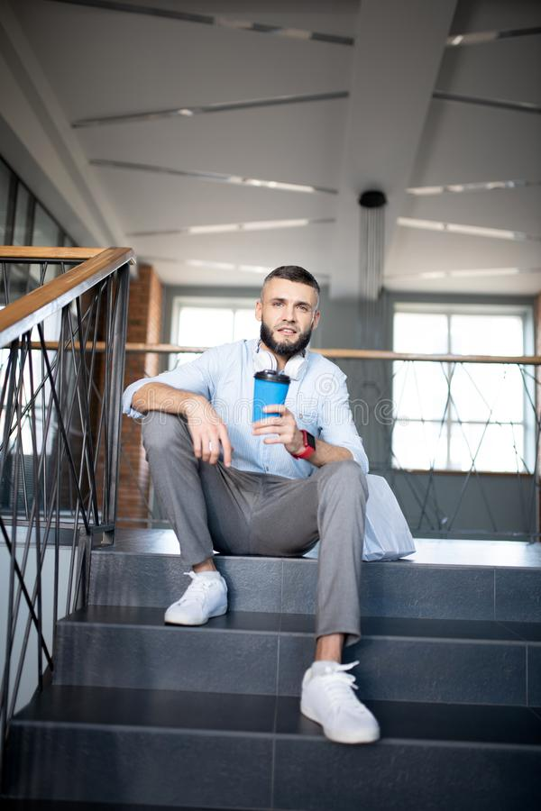 Office worker sitting on stairs and drinking takeaway coffee stock photography