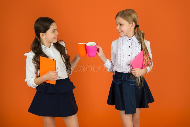 Drinking tea while break. School mates relaxing with drink. Enjoy being pupil. Girls kids school uniform orange. Background. Schoolgirl hold book or notepad and royalty free stock photos