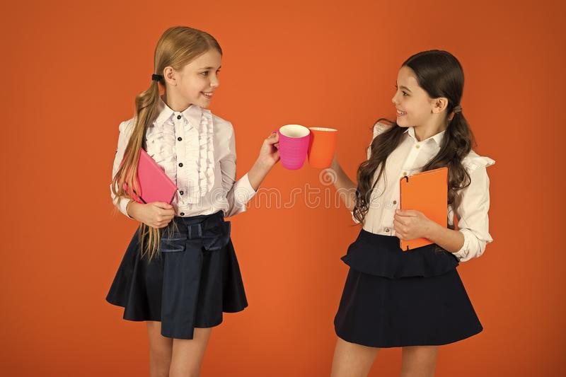 Drinking tea while break. School mates relaxing with drink. Enjoy being pupil. Girls kids school uniform orange. Background. Schoolgirl hold book or notepad and stock photos