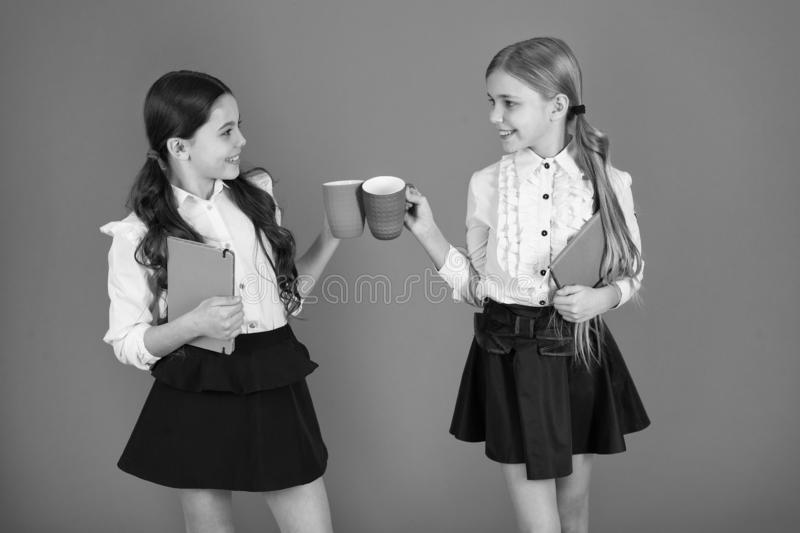 Drinking tea while break. School mates relaxing with drink. Enjoy being pupil. Girls kids school uniform orange. Background. Schoolgirl hold book or notepad and stock image