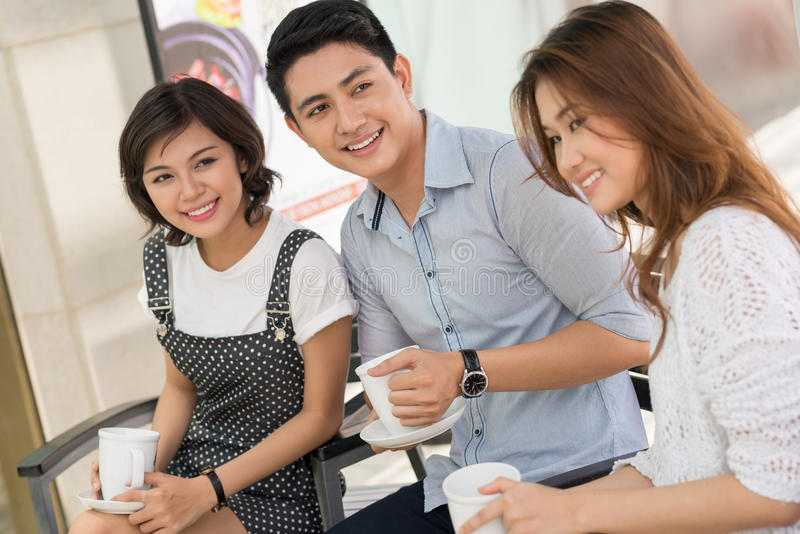Drinking tea. Friends sitting with tea-cups inside royalty free stock image