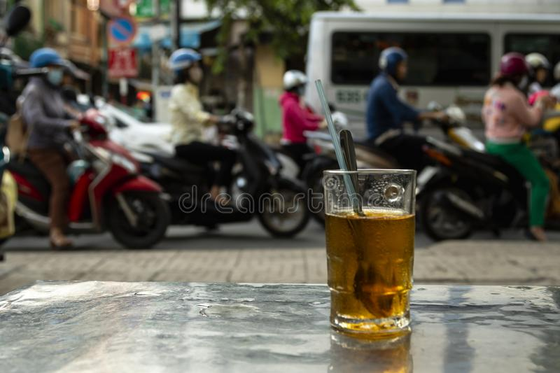 Drinking tea watching rush hour in Ho Chi Minh City Vietnam. Drinking tea watching rush hour of mopeds in Ho Chi Minh City Vietnam royalty free stock photo