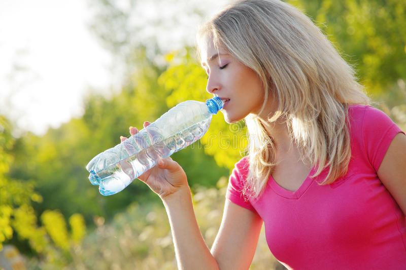 Drinking water. Young woman drinking after fitness at summer royalty free stock images