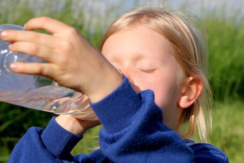 Drinking water. Little girl drinking water stock photography