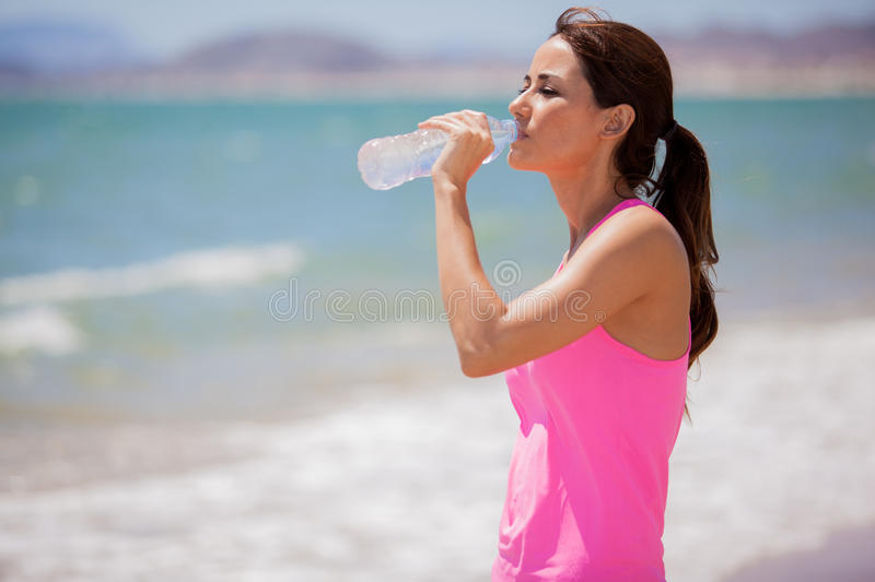Drinking water at the beach. Cute young woman taking a break from running and drinking water from a bottle royalty free stock photo