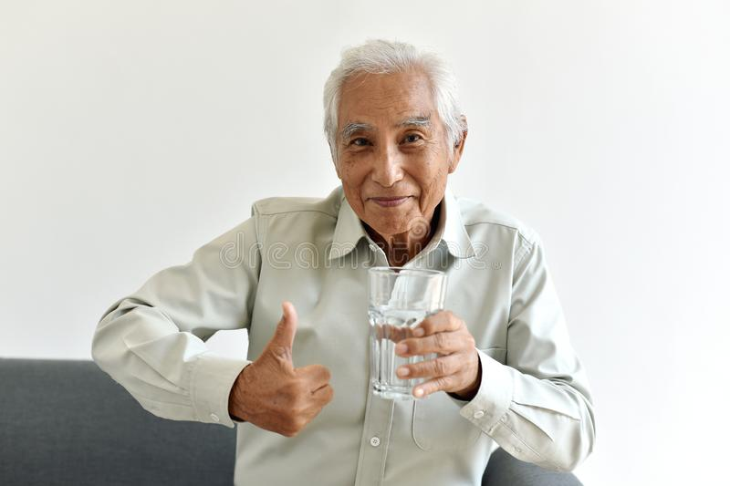 Drinking water is good healthy habit for old man, Elderly smiling asian man show thumb up to glass of purified water. royalty free stock image