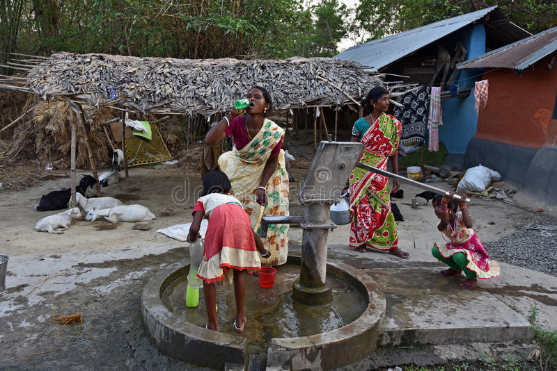 Drinking Water. Rampurhut,Birbhum,West Bengal,India,Asia-Women and children are busy to collect drinking water from a tube-well in a tribal village of West royalty free stock image