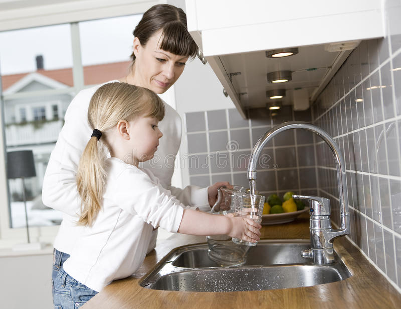 Drinking water. Small Girl in the kitchen with her mother drinking water