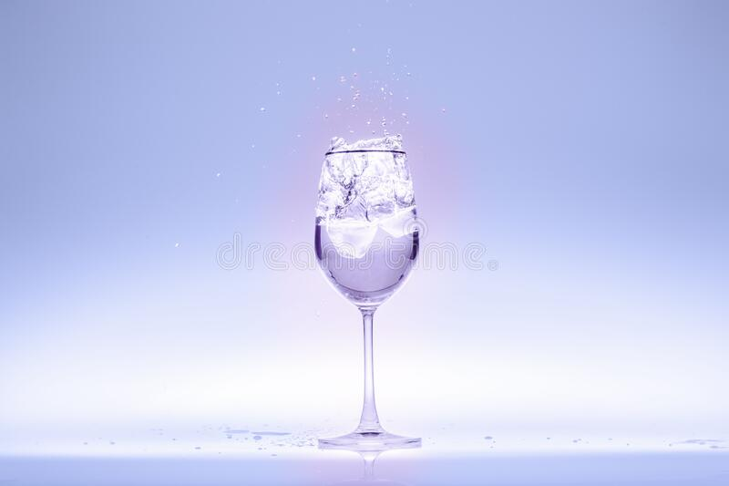 Drinking water in wine glass. Drinking water in a wine glass taken on a light blue background royalty free stock photo