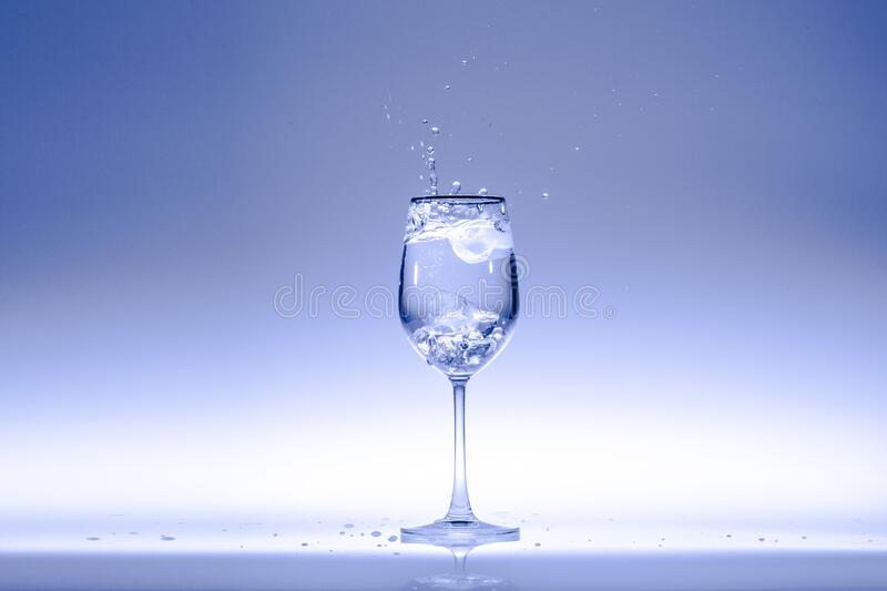 Drinking water in wine glass. Drinking water in a wine glass taken on a light blue background royalty free stock image